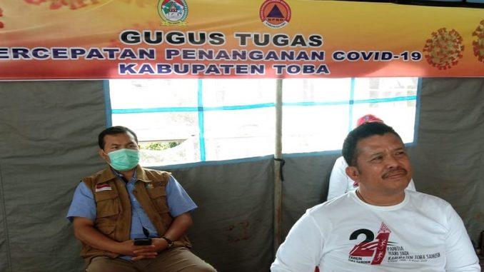 Ketua Gugus Percepatan Penanganan Covid-19 Kabupaten Toba, dr.Pontas Batubara didampingi Asisten Pemerintahan Toba ,Harapan Napitupulu di Posko Balige, Sabtu (28/3/2020).
