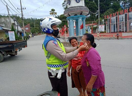 Tampak petugas memasangkan masker ke masyarakat saat gelar operasi Toba 2020