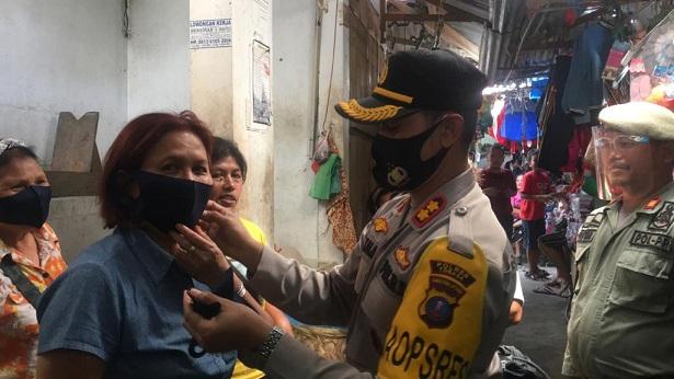 Kapolres Toba AKBP Akala Fikta Jaya S.I.K memakaikan masker ke masyarakat, (09/09/2020) sekira pukul 08.00 Wib