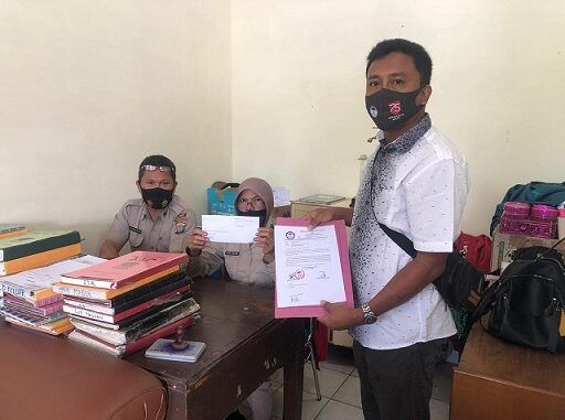 Ket;foto, ketua LPA kab karo Burhan Arif sembiring memperlihatkan bukti pelaporan ke Polres Tanah Karo, foto ,terkelin bukit.