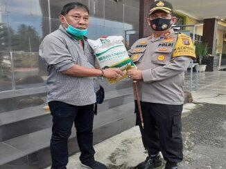 Kapolres Batu Bara pada saat menyerahkan bingkisan kepada wartawan di Polres Batu Bara, Senin (28/12/2020).