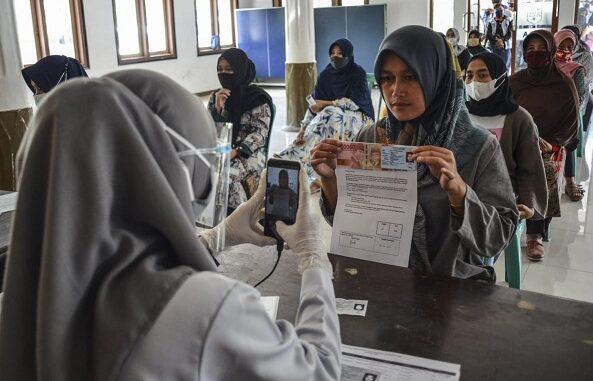 Petugas memotret identitas penerima bantuan sebagai tanda bukti saat penyaluran bantuan sosial (bansos) di Kantor Desa Sindangherang, Kabupaten Ciamis, Jawa Barat. Foto: Antara foto/ Adeng Bustomi