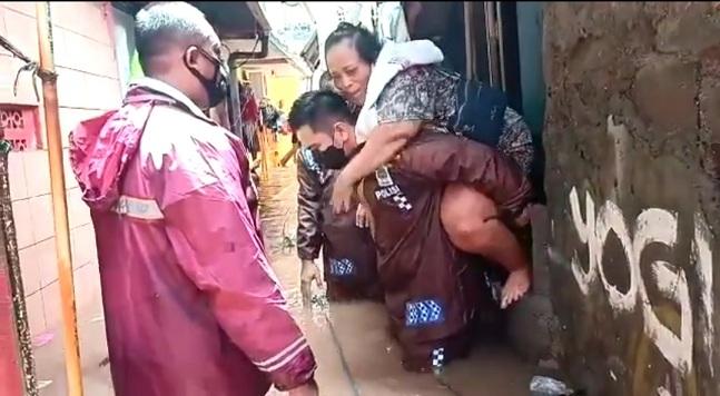 Kapolsek Cilandak Jakarta Selatan AKP Iskandarsyah mengevakuasi warga yang rumahnya terendam banjir, Minggu (21/2/2021). Photo : HumsPolri